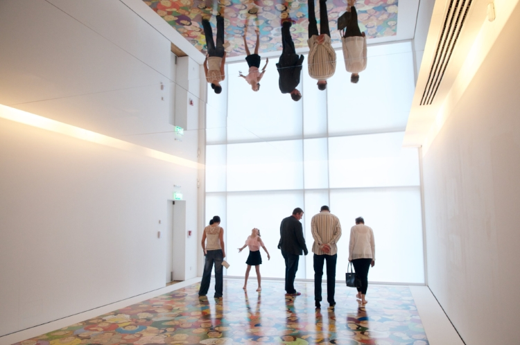 Image of a group enjoying an exhibit by artist NS Harsha at the Glynn Vivian Art Gallery. Four adults look at an image on the floor while a child looks up at the reflection on the ceiling