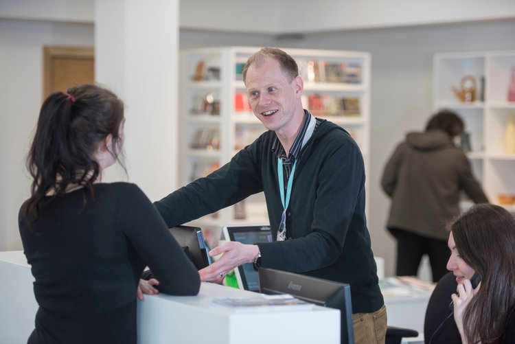 A member of staff giving information to a visitor at the reception of the Glynn Vivian Art Gallery