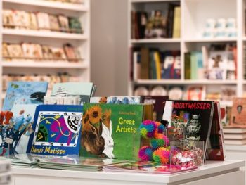 Shop table with illustrated books about great artists and art and other items to purchase from the Glynn Vivian Art Gallery shop